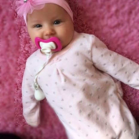 happy baby girl pretty in pink with pink iiamo soother