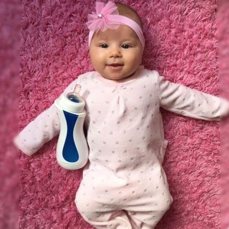 süßes kleines Baby in rosa mit iiamo go Babyfläschchen in weiß-blau
