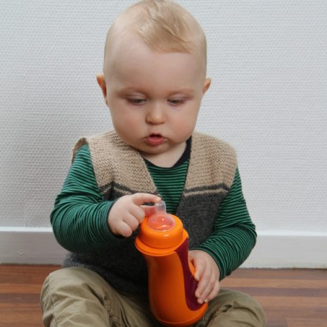 toddler explores his iiamo baby drinking bottle in orange