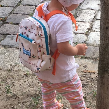 Girl going to the kindergarten with her Pink Lining Mini Rucksack it's a dog's life