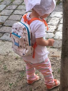 Little Girl on the way to kindergarten with Pink Lining Mini Rucksack it's a dog's life