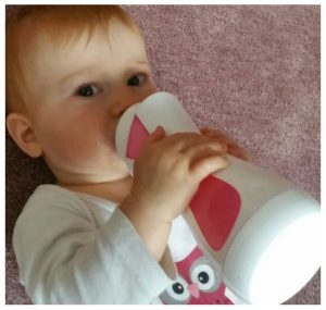 girl drinking warmed milk with iiamo go baby bottle