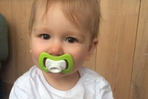 babygirl with green iiamo peace pacifier