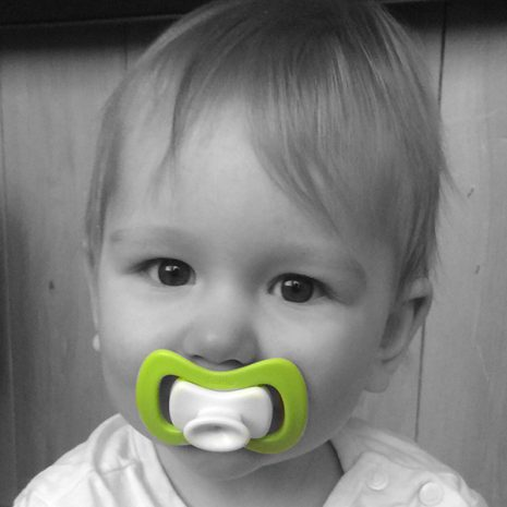 baby with beloved iiamo soother in green